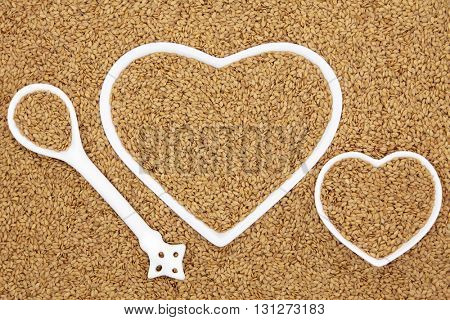 Golden flax seed health food in heart shaped porcelain bowls and spoon forming an abstract background.