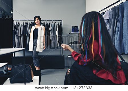 Pretty Asian woman showing her outfit to the friend