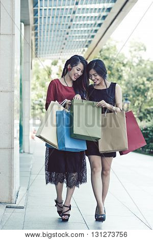 Happy young woman with many shopping bags walking outdoors