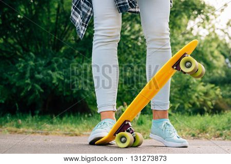 Girl In Jeans And Sneakers Standing In A Park Next To Yellow Skate