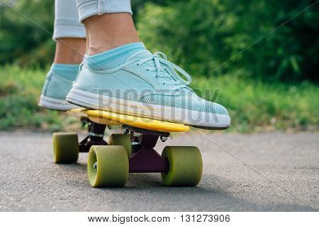 Female Feet In Sneakers On A Yellow Skateboard Closeup