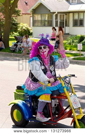 WEST ST. PAUL, MINNESOTA - MAY 21, 2016: Clown in costume riding motorized scooter entertains crowd during annual West St. Paul Days Grande Parade in West St. Paul on May 21, 2016.