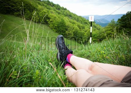 Legs of woman hiker sitting on top of a high mountain above a green forest. Freedom concept