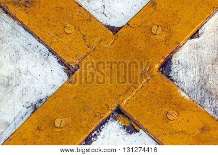 Close Up Of Rustic Yellow Metal Cross