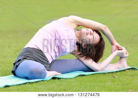 portrait of Japanese woman outside doing stretches exercise