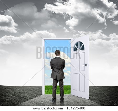 Businessman standing in grey reality with door in colorful nature