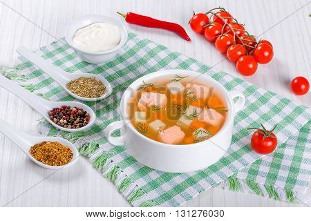 salmon soup with vegetables and dill in a white bowl on a table cloth on an rustic table with cherry tomatoes and cream in a gravy boatview from above close-up