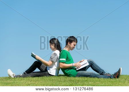 Asian couple student reading book together at outdoors park in university