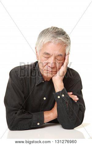 studio shot of senior Japanese man sleeping on the table on white background