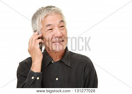 studio shot of senior man with a smart phone on white background