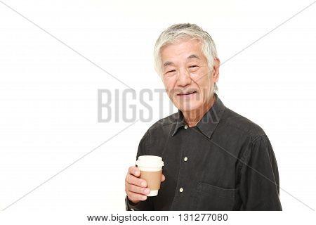 studio shot of senior Japanese man takes a coffee break on white background