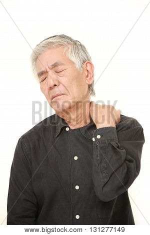 studio shot of senior Japanese man suffers from neck ache on white background