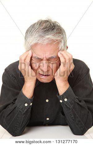 studio shot of senior Japanese man suffers from headache on white background