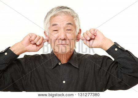 studio shot of senior Japanese man suffers from noise on white background
