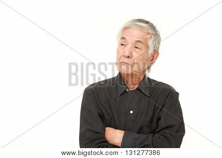 studio shot of senior Japanese man worries about something on white background