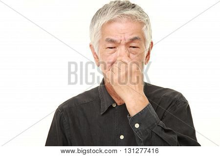 studio shot of senior Japanese man holding his nose because of a bad smell on white background