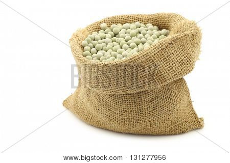 green peas in a burlap bag on a white background