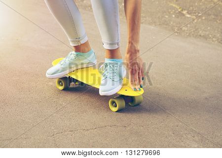 Girl rides on the road on a plastic skateboard in the sunlight yellow colors