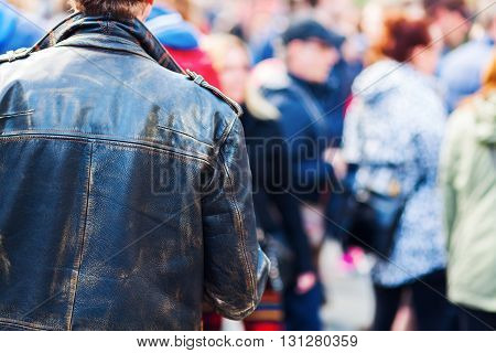 man with leather jacket in a crowd of people