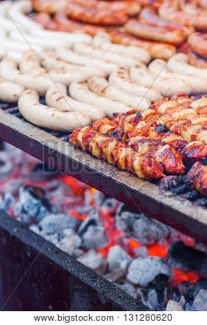 bratwurst and skewers on a large grill