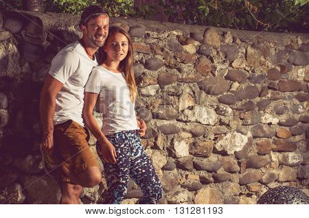 Happy young couple sitting outdoor near stone wall and smiling as relationship concept
