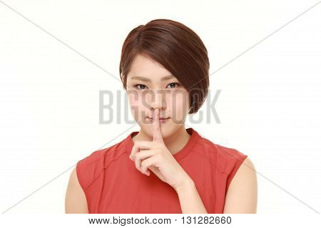 young Japanese woman with silence gestures on white background