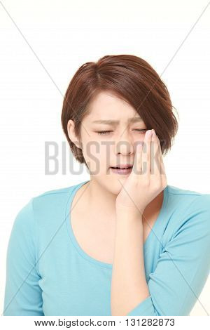 studio shot of young Japanese woman suffers from toothache