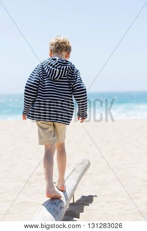 back view of positive happy boy walking on the old trunk at the beach being active and playful at the beach
