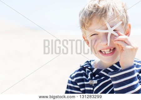 portrait of beautiful smiling happy boy winking and covering his eye with starfish at the beach vacation and lifestyle concept copyspace on the side