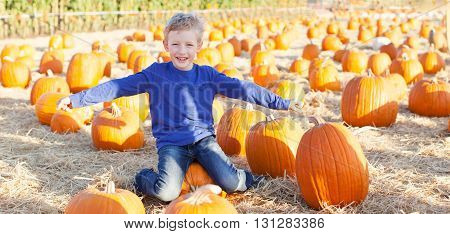 panorama of positive cheerful boy enjoying pumpkin patch at fall pretending to be a plane being playful