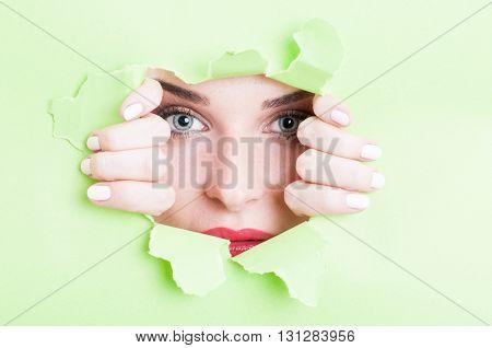 Beautiful Woman Looking Thru Torn Green Cardboard
