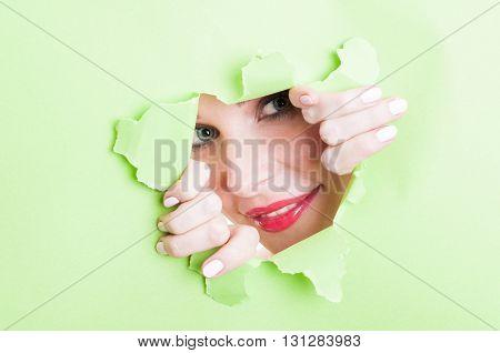 Female Model Looking Thru Ripped Green Cardboard