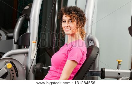 Attractive Female Smiling And Exercising In The Gym