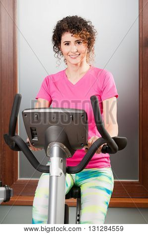 Beautiful Woman Smiling And Using Stationary Bicycle