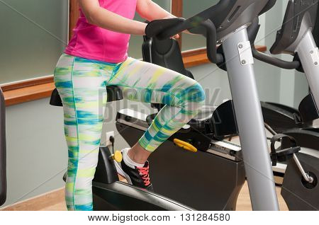 Young Female Legs Training And Riding The Stationary Bicycle