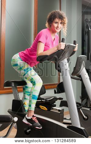 Young Woman Smiling And Riding The Stationary Bicycle