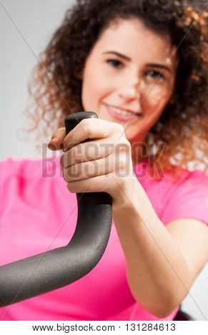 Beautiful Female Smiling And Holding A Stationary Bike Handle