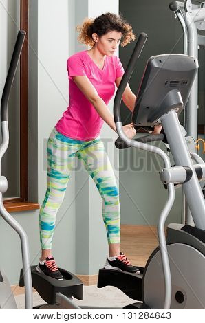Young Female With Sportswear Exercising On Stepper