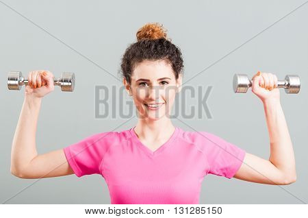 Young Smiling Woman Exercising For Deltoid With Dumbells