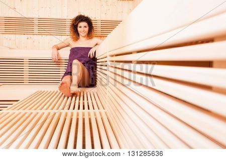 Beautiful Woman Relaxing And Smiling In A Wooden Sauna