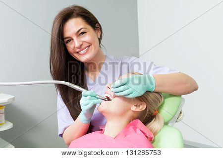 Friendly Female Dentist Drilling Patient Tooth