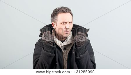 Sexy Man Frowning And Holding His Jacket Collar