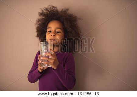Cute little african american girl drinking water.