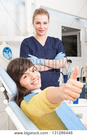 Doctor and patient giving thump up at dentist office acting confident and happy