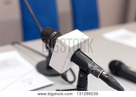 Microphone in focus against blurred background. Microphone at press conference.