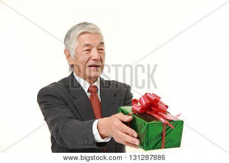 studio shot of senior Japanese businessman offering a gift