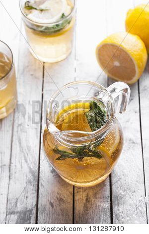 Fresh lemonade in a glass jug on a white background