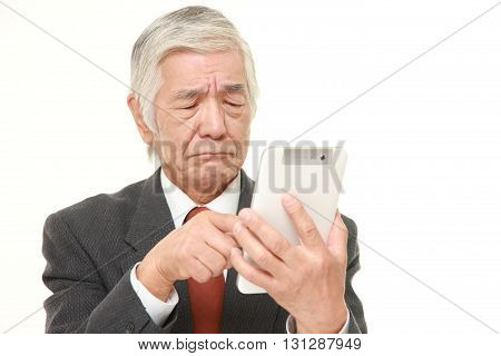 portrait of senior Japanese businessman using computer looking confused on white background