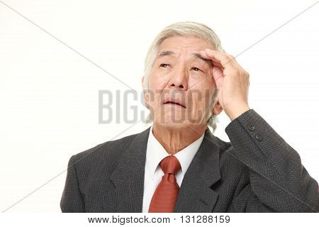 portrait of senior Japanese businessman has lost his memory on white background