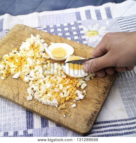 Chef hand chopping egg with a kitchen knife on a wooden tray outdoor closeup shot
